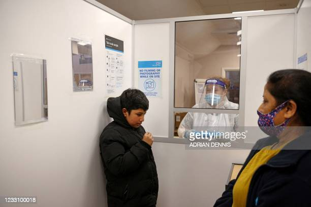 Youth uses a swab to take a sample from his nostril at a NHS Test and Trace Covid-19 testing unit at the Civic Centre in Uxbridge, Hillingdon, west...