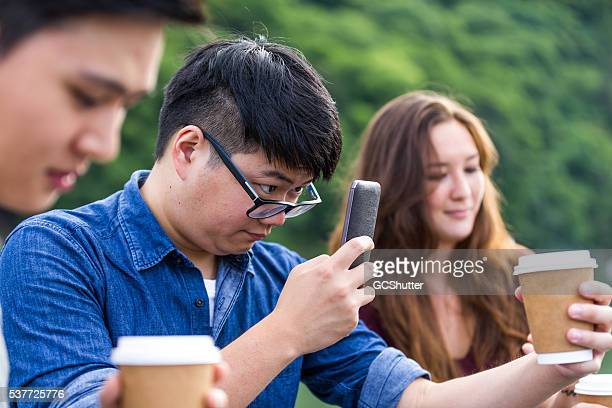 Youth using his phone while holding a coffee cup
