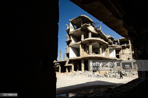 Youth walks by damaged buildings in the Syrian Kurdish town of Kobane, also known as Ain al-Arab, in the north of Aleppo governorate on February 25,...