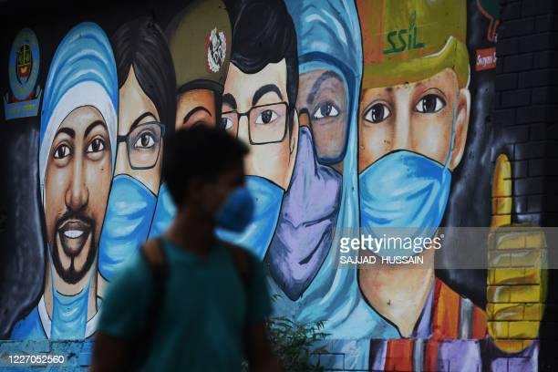 A youth walks past a mural of frontline workers after the government eased a nationwide lockdown imposed as a preventive measure against the COVID19...