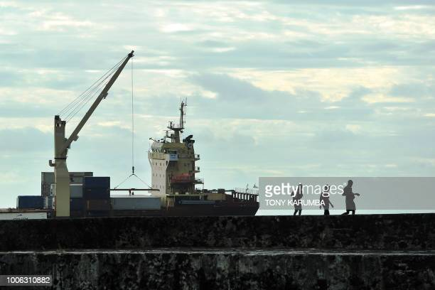 Youth wander along a section of port wall at Moroni on July 27 2018 where an upcoming referendum has caused political tensions in the volcanic...