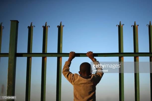 A youth watches children playing football in Alexandra township on July 1 2013 in Johannesburg South Africa Antiapartheid icon and Nobel Peace Prize...