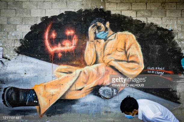 TOPSHOT A youth wearing a protective mask walks past a mural reading We are tired in the Lebanese northern city of Tripoli on April 28 2020 Lebanon...