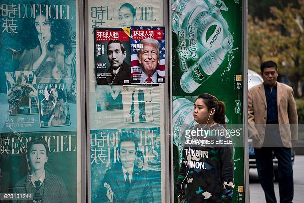 A youth wearing a shirt that reads 'we have nothing in common' walks past a news stand advertising local Chinese magazine Global People showing cover...