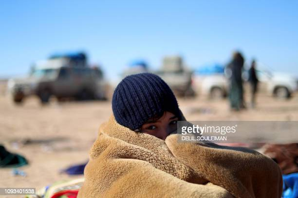 Youth who fled fighting between Syrian Democratic Forces and Islamic State jihadists in the frontline Syrian village of Baghuz, keeps warm as they...