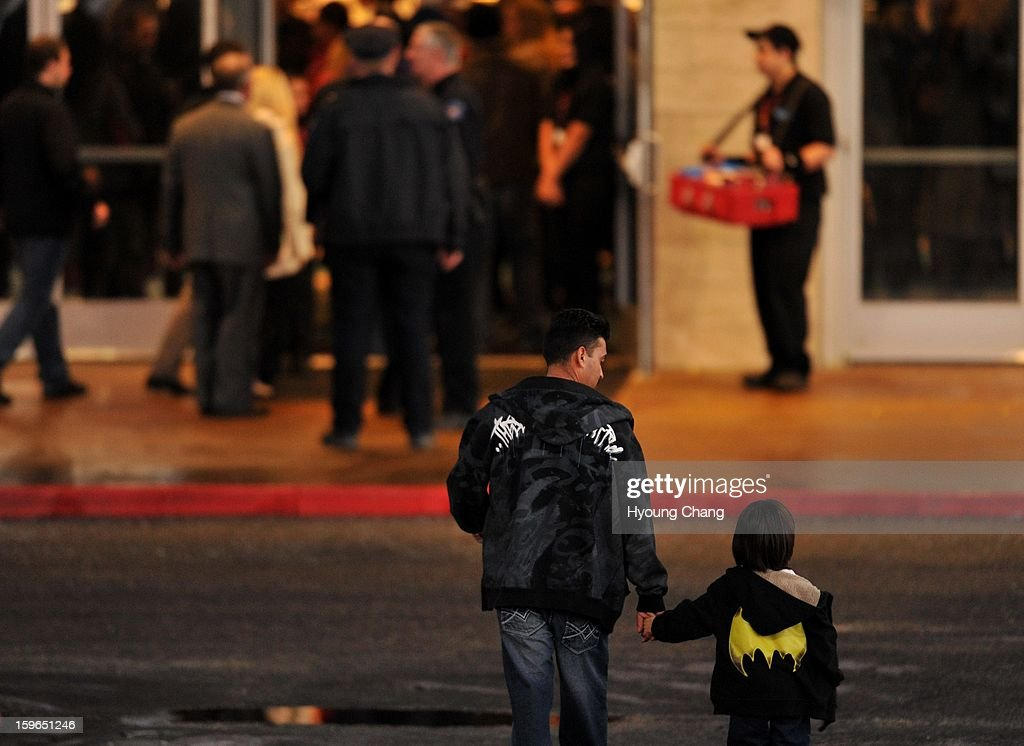 A youth with Batman Logo shirts, front right, is escorted to the theater by a man to the Century Aurora. The movie theater where a gunman killed 12 people and wounded dozens of others reopened with a private ceremony for victims, first responders and officials.