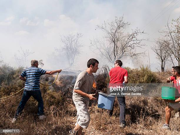 Youth with buckets and hoses off the fire of a wildfire that is on the same street a few meters of the village houses. Bocairent, , Spain