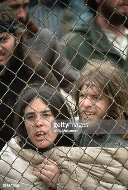 A youthful couple arrested in the 1971 'May Day' demonstrations comfort one another while being held in an outdoor jail the Washington Redskins...