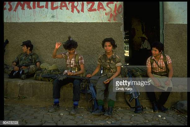 Youthful FMLN girl guerrillas sitting by wall w male comrades poised w rifles during mil offensive in eastern El Salvador