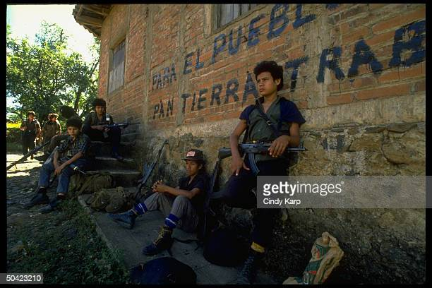 Youthful FMLN guerrillas incl girls sitting by graffitiscrawled wall poised w rifles during mil offensive in eastern El Salvador