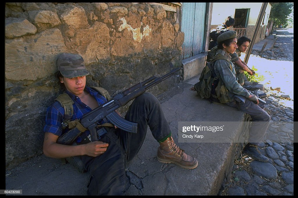 Youthful FMLN guerrillas sitting by wall : News Photo