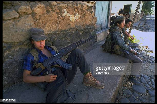 Youthful FMLN guerrillas sitting by wall poised w rifles during mil offensive in eastern El Salvador