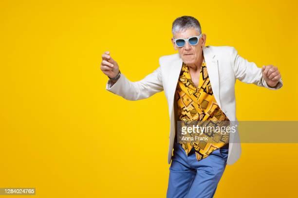 junger alter mann in den sechziger jahren mit spaß und tanz - cheerful stock-fotos und bilder