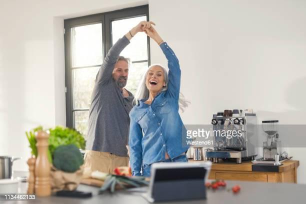 youthful senior couple dancing in the kitchen - mann 60 jahre stock-fotos und bilder