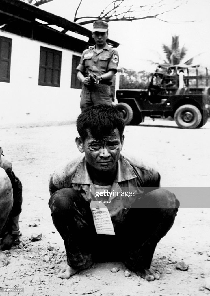 A youthful Viet Cong soldier, heavily guarded, awaits interrogation following capture in the attacks on the capital city during the Tet Offensive of 1968.