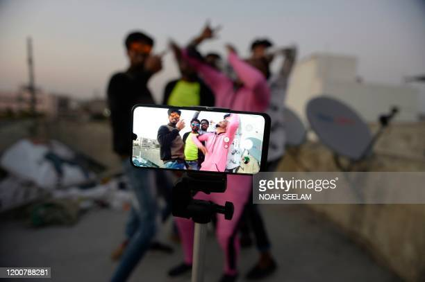 Youths act in front of a mobile phone camera while making a TikTok video on the terrace of their residence in Hyderabad on February 14, 2020.