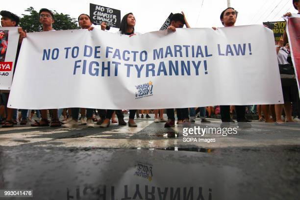 Youths are seen holding a huge banner during the protest Youth groups protest against the alleged human rights violation of the current...