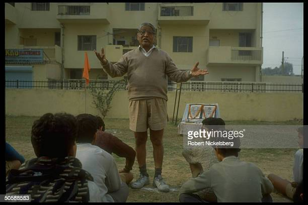 Youths being lectured sitting outside in early AM physical training shaka of RSS Rashtriya Swayamsevak Sangh Hindu cultural org