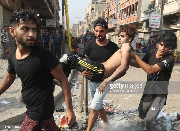 TOPSHOT Youths carry away a protester injured during clashes with riot police amidst demonstrations against state corruption failing public services...