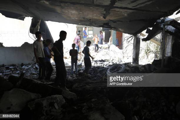 Youths check the house of a Palestinian man who took part in an attack in Jerusalem in which an Israeli policewoman was killed two months ago after...