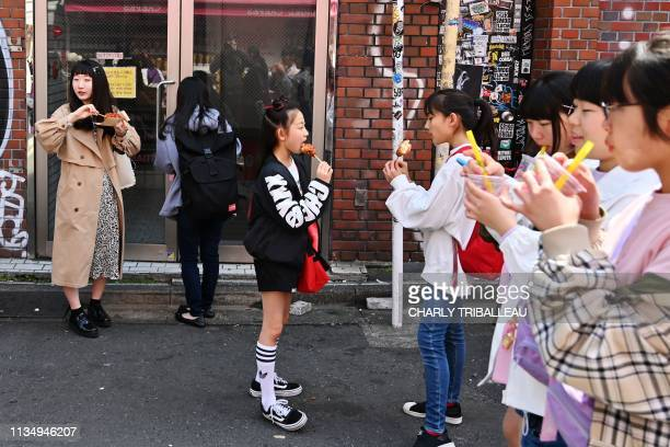 Youths eat and drink snacks on a sunny day in Tokyo's Harajuku district on April 5 2019