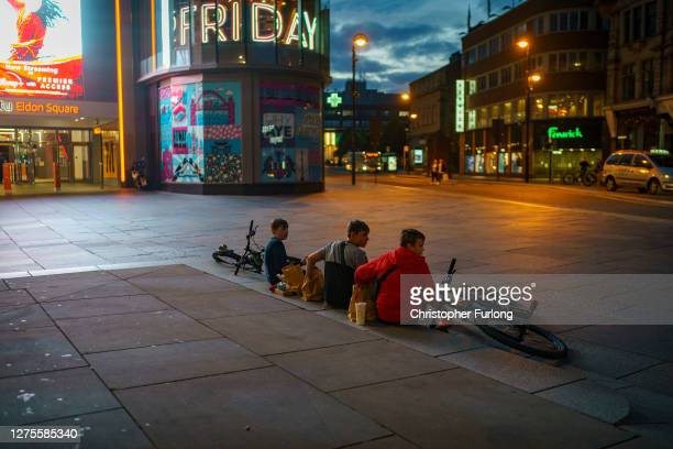 Youths eat takeaway food on the empty streets of Newcastle as the localised lockdown comes into force on September 18 2020 in Newcastle upon Tyne...