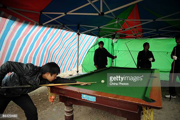Youths from the earthquake hit Province of Sichuan play snooker in a tent at the Hongbai Township on January 23, 2009 in Shifang of Sichuan Province,...