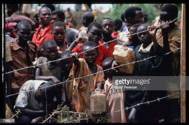 Youths gather behind the fence of a refugee camp May 3 1994 at the border of Rwanda and Tanzania Hutu refugees have fled to Tanzania across the...