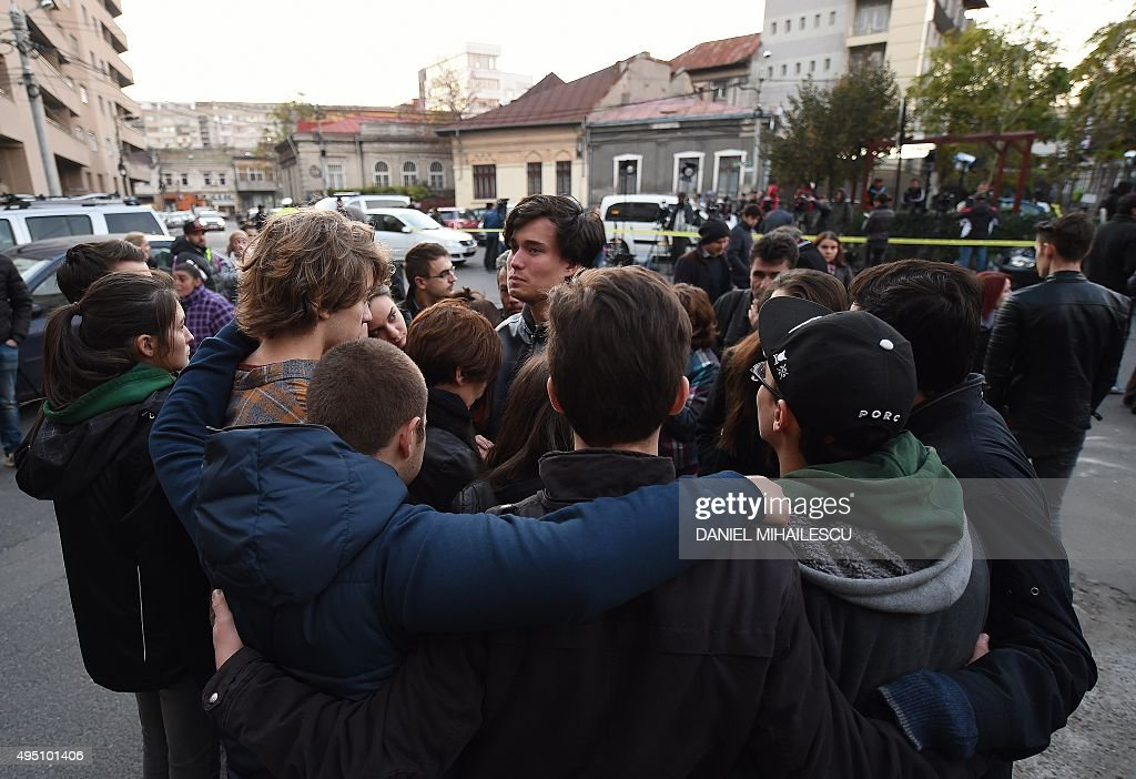 Youths hold each other as they commemorate a friend among the victims outside the nightclub Colectiv in Bucharest on October 31, 2015, a day after a mortal fire. At least 27 people were killed and more than 160 injured after a fire ripped through a nightclub in Bucharest late on Friday, in one of the worst accidents to hit the Romanian capital. MIHAILESCU