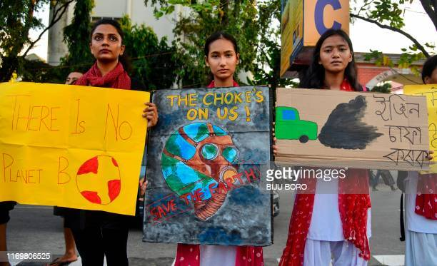 Youths hold placards as they participate in a protest against governmental inaction towards climate breakdown and environmental pollution, part of...