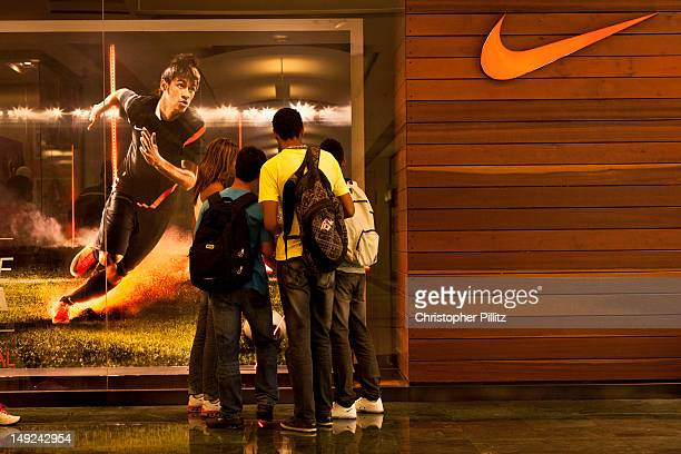 Youths look at the window display of a Nike store in Rio de Janeiro Brazil with the big star of the moment Neymar 11th April 2012