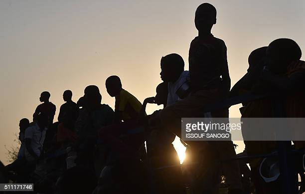 Youths observe supporters of Niger's leading opposition figure and contender for the February 21 presidential election Hama Amadou jailed since...