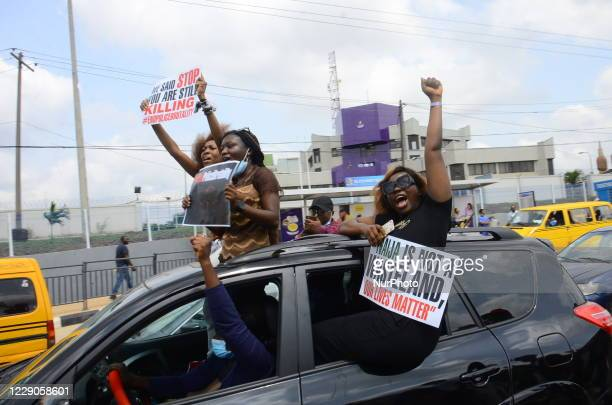 Youths of ENDSARS protesters display their placards in a car in support of the ongoing protest against the harassment, killings and brutality of The...