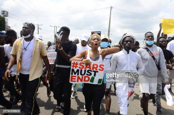 Youths of ENDSARS protesters display their placards in a crowd in support of the ongoing protest against the harassment, killings and brutality of...