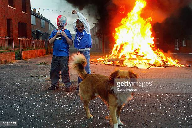 Youths pictured beside an Eleventh Night Bonfire on July 11 2003 in the Tigers Bay area of North Belfast Northern Ireland The bonfires which are...