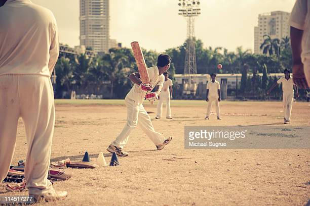 Youths play cricket in an open field in India.