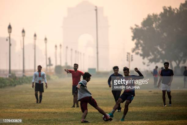 Youths play football along Rajpath near India Gate under heavy smog conditions in New Delhi on November 3, 2020.