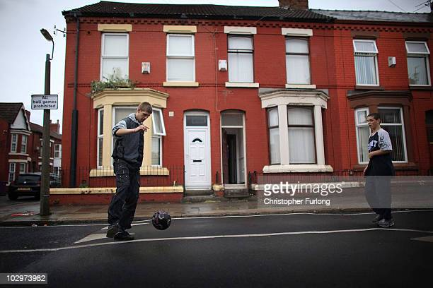 Youths play football in the street in Liverpool where today British Prime Minister David Cameron launched the conservative's big society drive on...