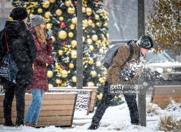 Youths play next to a Christmas tree as it snows in downtown Moscow on December 13 2018