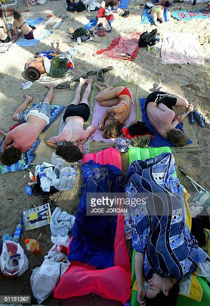 Youths rest 07 August 2004 on the beach in the northern Spanish town of Benicassim where the International Festival of Benicassim AFP PHOTO / JOSE...