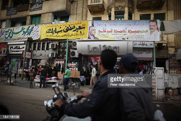 Youths ride a scooter past shops festooned with election banners on November 26 2011 in Cairo Egypt Thousands of Egyptians are continuing to occupy...