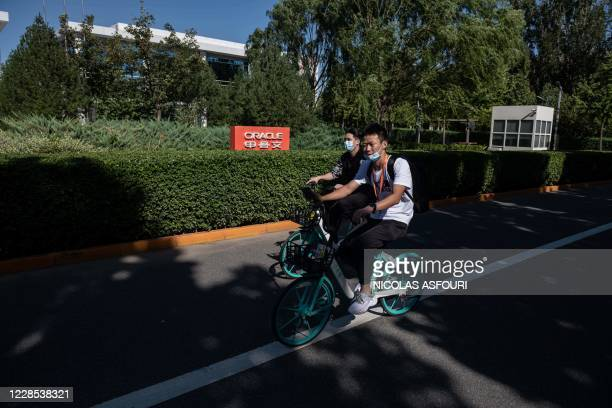 Youths ride bicycles past the office building for US-based technology company Oracle in Beijing on September 16, 2020. - Silicon Valley tech giant...