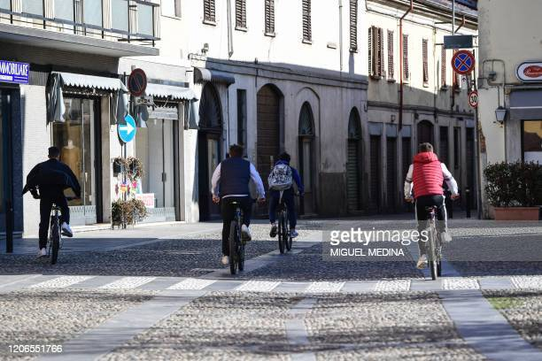 Youths ride their bicycle through a deserted street in Codogno southeast of Milan on March 11 2020 a day after Italy imposed unprecedented national...