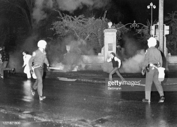 Youths run from tear gas thrown by police to break up a window smashing rampage by students of Kent State University demonstrating the war.