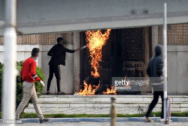 Youths set tires ablaze at the entrance of a shrine dedicated to the late Iraqi Shiite Ayatollah Mohammed Baqir alHakim during antigovernment...