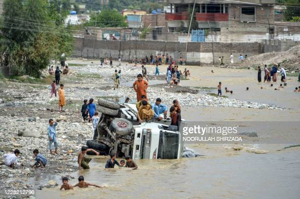 Youths sit on an overturned vehicle after flash floods triggered by heavy rainfalls affected the area in Jalalabad on August 26, 2020. - Rescue...