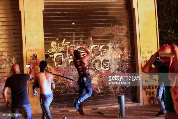 Youths smash the facade of a shop during a demonstration against dire economic conditions in the downtown district of the Lebanese capital Beirut,...