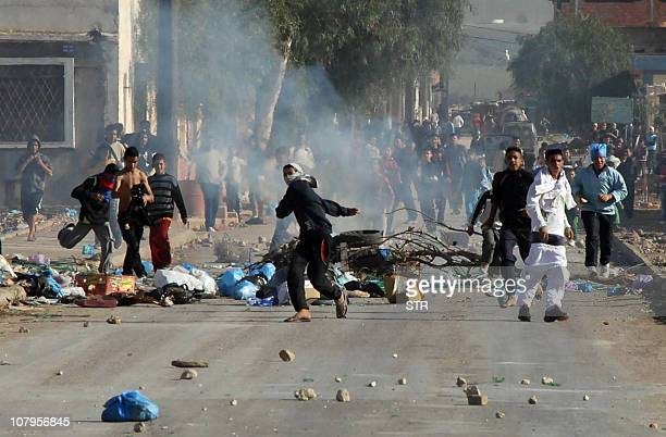 Youths throw objects during clashes on January 6 2011 in the Amel district of Oran some 430 kilometres west of the capital Riots erupted in Algeria...