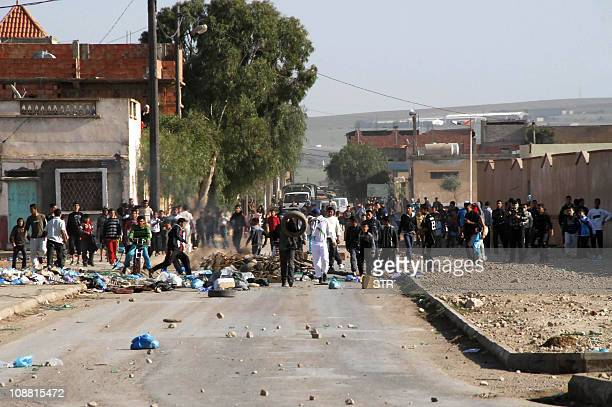 Youths throw objects during clashes on January 6 2011 in the Amel district of Oran some 430 kilometres west of the Algiers Riots erupted in Algeria...