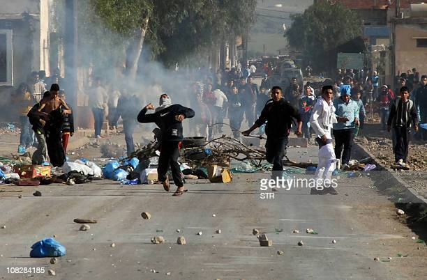 Youths throws objects during clashes on January 6 2011 in the Amel district of Oran some 430 kilometres west of the capital Riots erupted in Algeria...